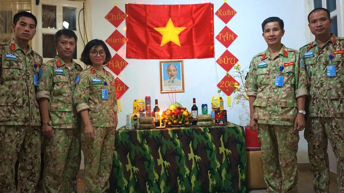 Trung tá Lưu Đình Hiến, tổ trưởng tổ công tác, Chỉ huy trưởng Lực lượng Việt Nam tại phái bộ Gìn giữ hòa bình Liên Hợp Quốc ở Cộng hòa Trung Phi (thứ hai từ phải qua) cùng đồng đội bên bàn thờ Chủ tịch Hồ Chí Minh ngày Tết. Ảnh: Nhân vật cung cấp