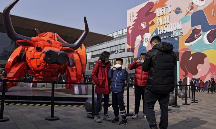 Người đàn ông và bé trai đeo khẩu trang sau khi chụp ảnh gần biểu tượng chú trâu của năm Tân Sửu tại trung tâm mua sắm nổi tiếng ở Bắc Kinh hôm mùng một Tết. Ảnh: AP.
