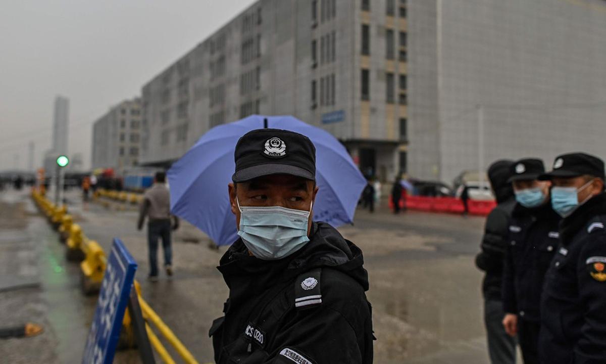 Bảo vệ đứng bên ngoài chợ hải sản Hoa Nam ở thành phố Vũ Hán khi nhóm của WHO tới điều tra hôm 31/1. Ảnh: AFP.