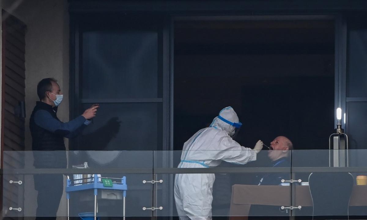 Nhân viên y tế Trung Quốc lấy mẫu xét nghiệm Covid-19 cho một thành viên nhóm điều tra của WHO tại Vũ Hán, ngày 8/2. Ảnh: AFP.