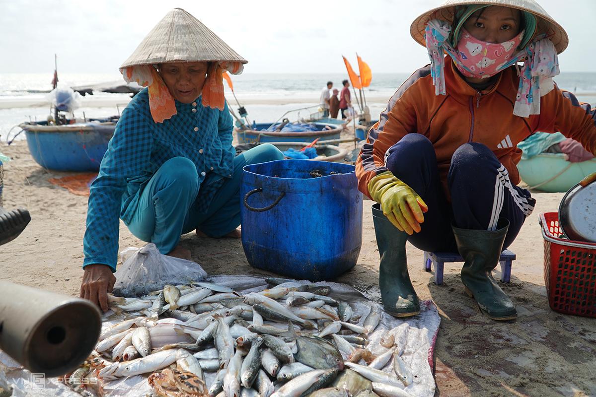 Người dân bày cá bên bờ biển bán cho du khách. Ảnh: Trường Hà.