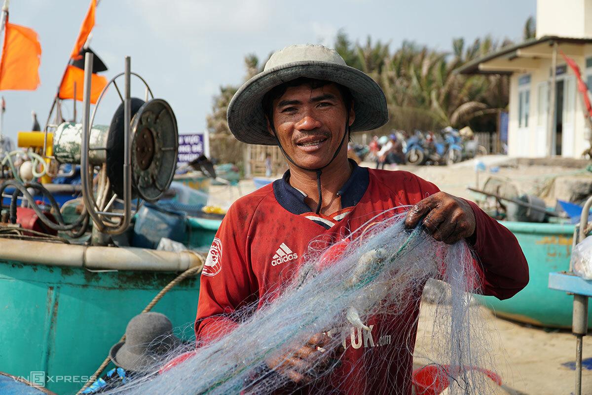 Ông Nguyễn Văn Lưỡng đang gỡ cá sau chuyến đi biển sáng mùng 3 Tết. Ảnh: Trường Hà.