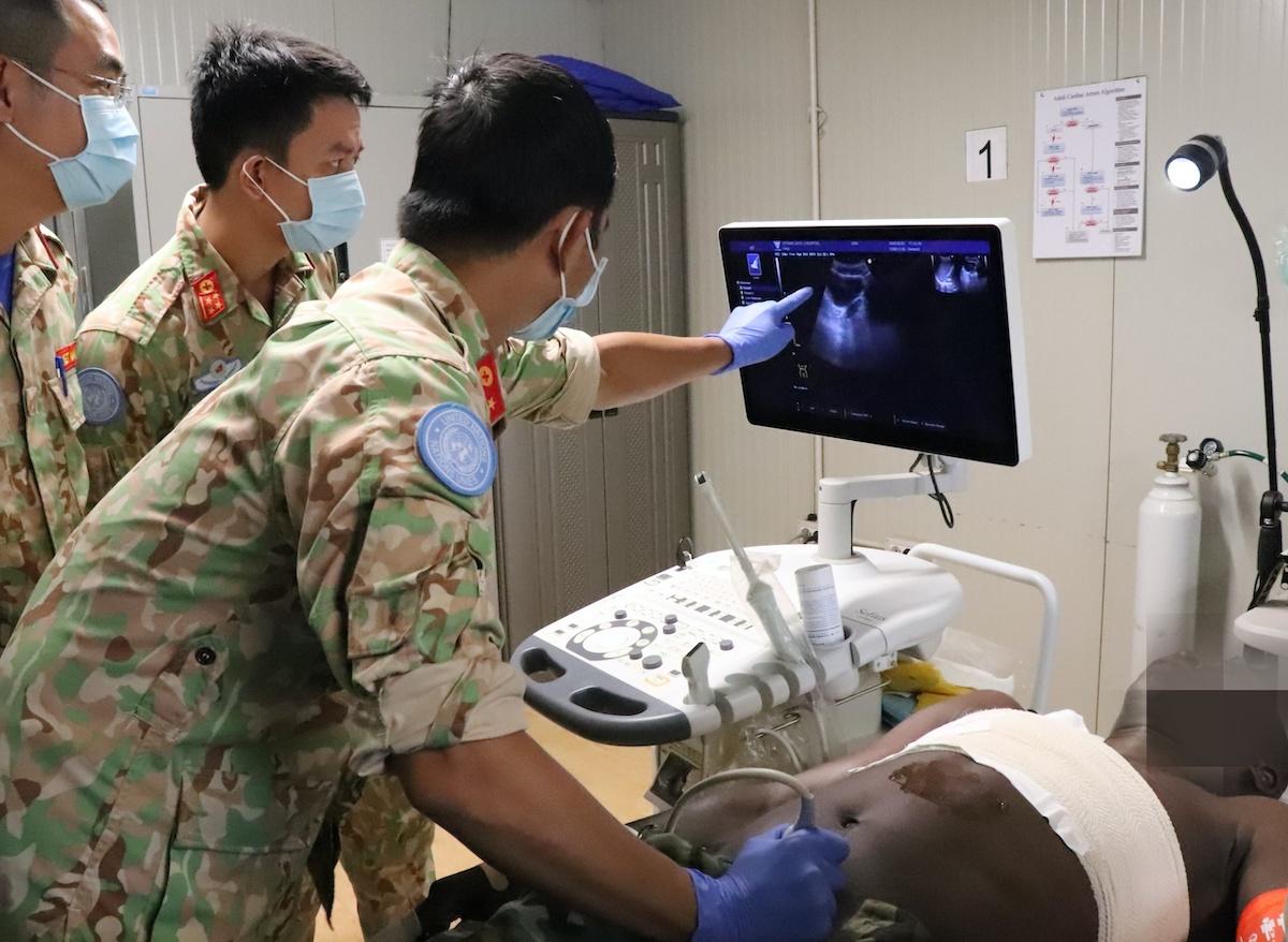 Các bác sĩ bệnh viện dã chiến 2.2 của Việt Nam thăm khám cho bệnh nhân nam 44 tuổi của Tiểu đoàn bộ binh Ghana, bị Vết thương thấu ngực. Ảnh: Quang Chiến