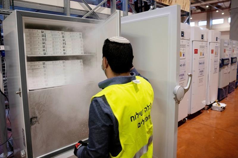 Nhân viên mở tủ chứa vaccine Pfizer/BioNTech tại Israel hồi tháng một. Ảnh: Reuters.