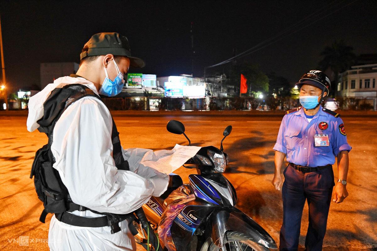 Lực lượng an ninh kiểm tra giấy tờ của người dân khi qua chốt kiểm dịch, đêm 15/2. Ảnh: Giang Huy