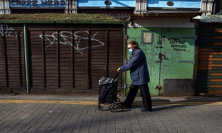 Người phụ nữ đi trên con phố vắng bóng người vì phong tỏa ngăn Covid-19 ở Chiswick, thủ đô London, Anh hôm 13/2. Ảnh: Reuters.