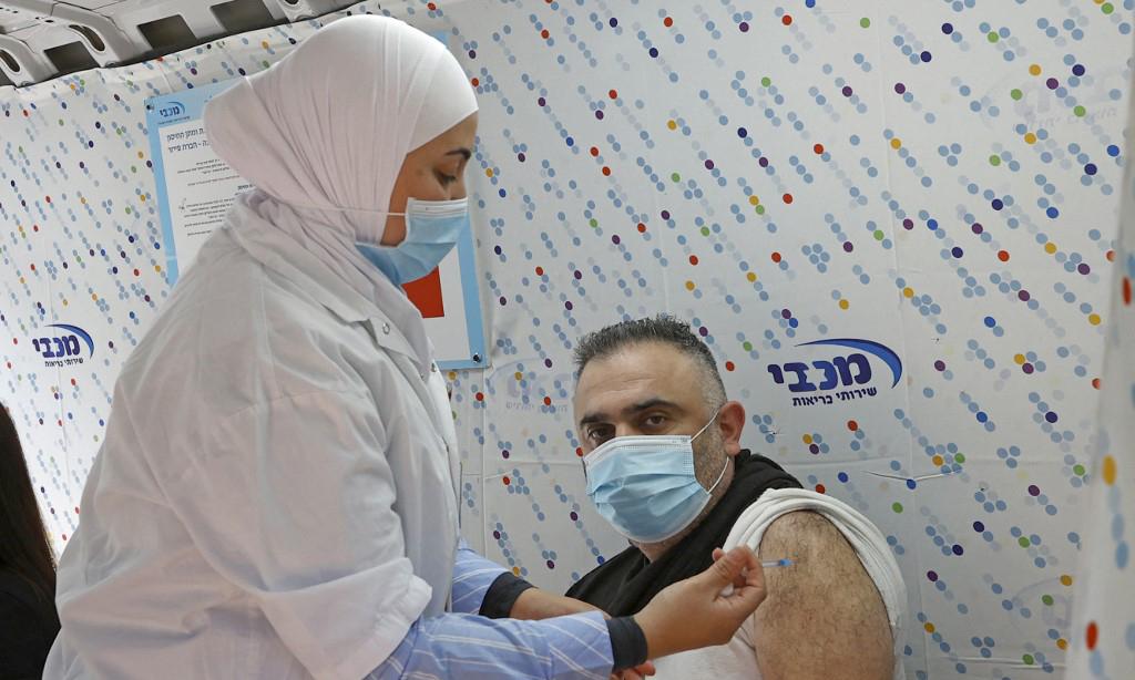 Nhân viên y tế tiêm vaccine Covid-19 của Pfizer-BioNTech cho một người đàn ông tại Tel Aviv, Israel, hôm 16/2. Ảnh: AFP.