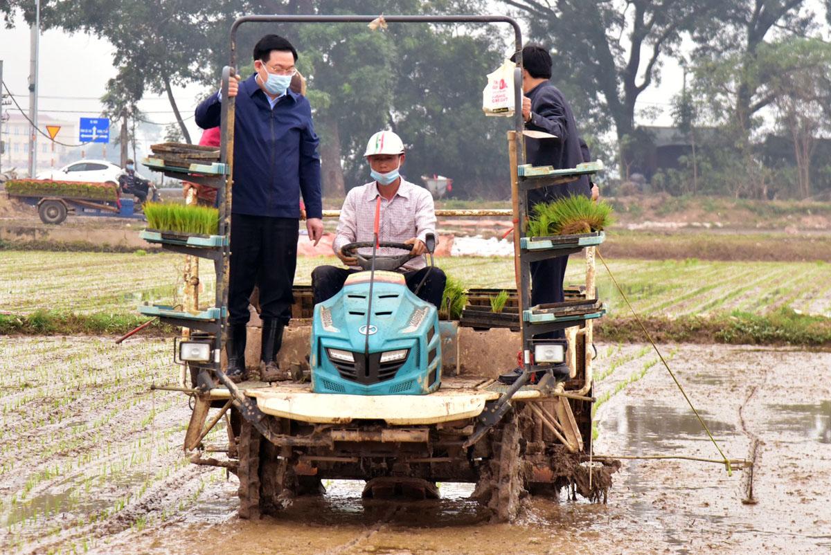 Ông Vương Đình Huệ sau đó trực tiếp lên máy cấy lúa cùng bà con nông dân. Ảnh: Viết Thành.