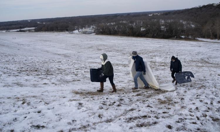 Người dân di chuyển trên một ngọn đồi phủ đầy tuyết ở Waco, Texas, hôm 18/2. Ảnh: AFP.