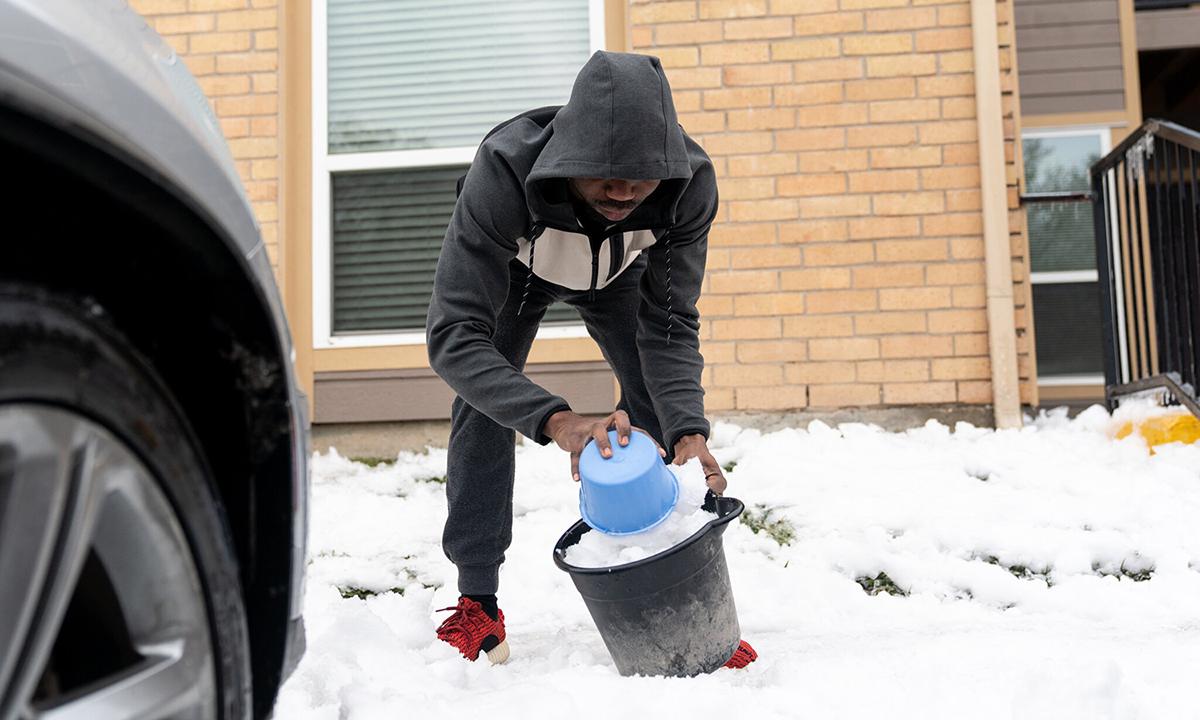 Một người dân lấy băng tuyết để đun lấy nước sử dụng ở ngoại ô Austin, bang Texas hôm 17/2. Ảnh: NYTimes.