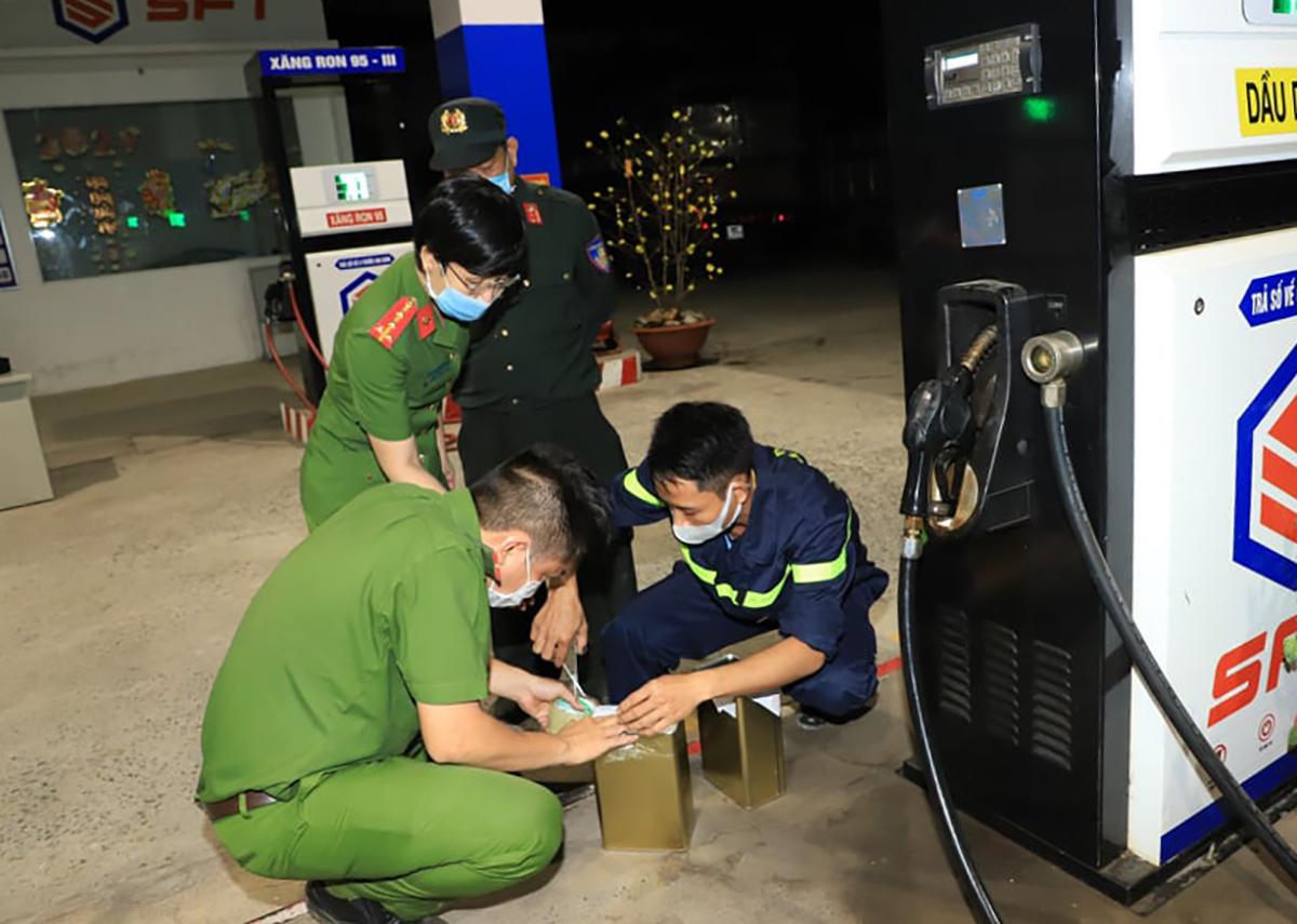 Cảnh sát niêm phong sau khi lấy mẫu một cây xăng trong đường dây buôn lậu, sản xuất xăng giả của Hữu. Ảnh: Thái Hà