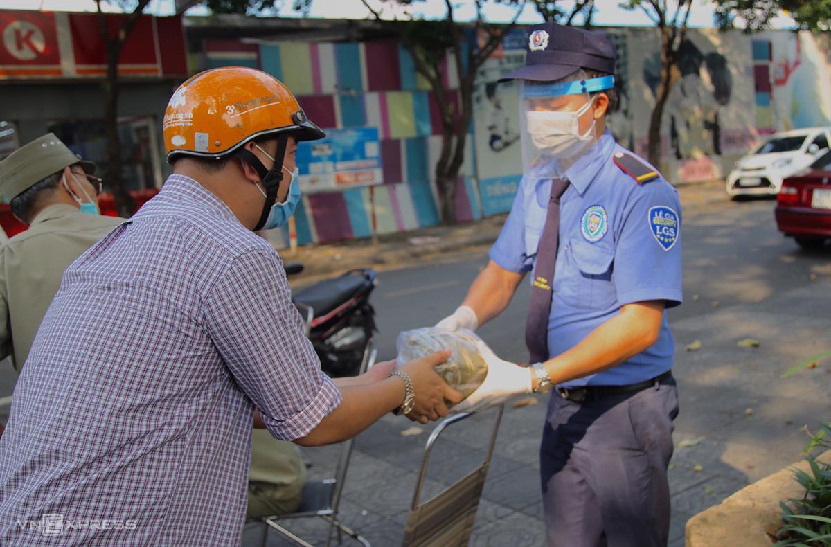 Người dân tiếp tế nhu yếu phẩm cho cư dân chung cư Carillon, quận Tân Bình bị phong tỏa hôm 9/2. Ảnh: Đình Văn.