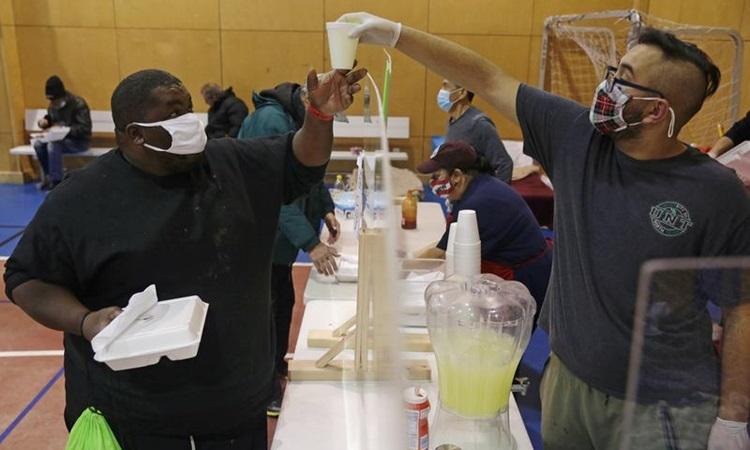 Tình nguyện viên phát bữa ăn tại một cơ sở cứu tế quân đội sau khi thời tiết mùa đông khắc nghiệt gây mất điện ở Plano, Texas hôm 18/2. Ảnh: Reuters.