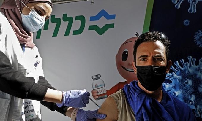 Nhân viên y tế tiêm vaccine Covd-19 của Pfizer/BioNtech cho người dân tại thành phố Petah Tikva, Israel ngày 1/2. Ảnh: AFP.