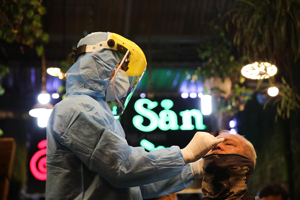Nhân viên y tế lấy mẫu phết mũi họng thực khách tại quán nhậu. Ảnh: Đình Văn.