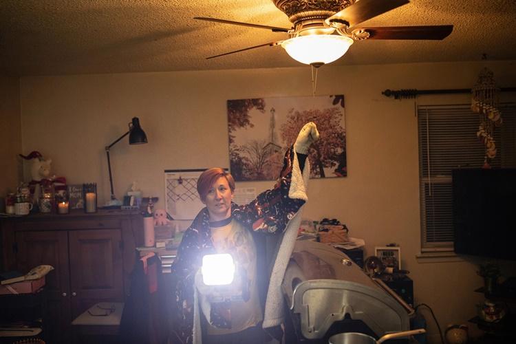 Heather Graham, một người dân ở Killeen. hôm 20/2 bật lại bóng đèn trong phòng khách ngôi nhà của mình sau 6 ngày mất điện. Ảnh: NYTimes.