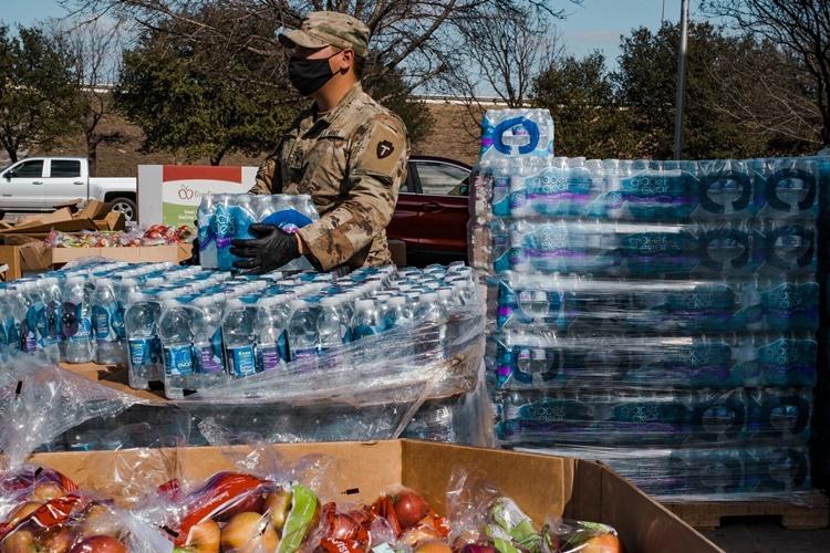 Thành viên Vệ binh Quốc gia hỗ trợ phát thực phẩm, nước uống tại một điểm phân phối ở San Antonio ngày 20/2. Ảnh: NYTimes.