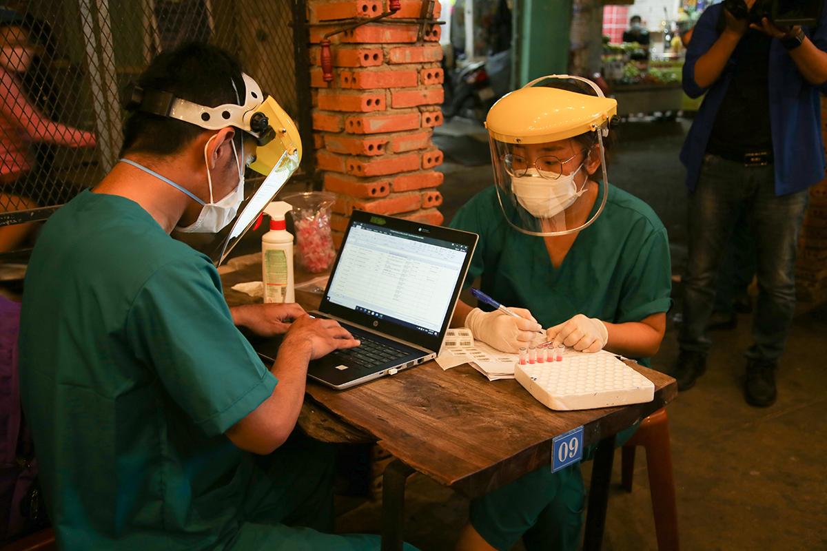 Nhân viên y tế ghi chép, nhập thông tin người được lấy mẫu xét nghiệm vào phần mềm giám sát dịch bệnh. Ảnh: Đình Văn.