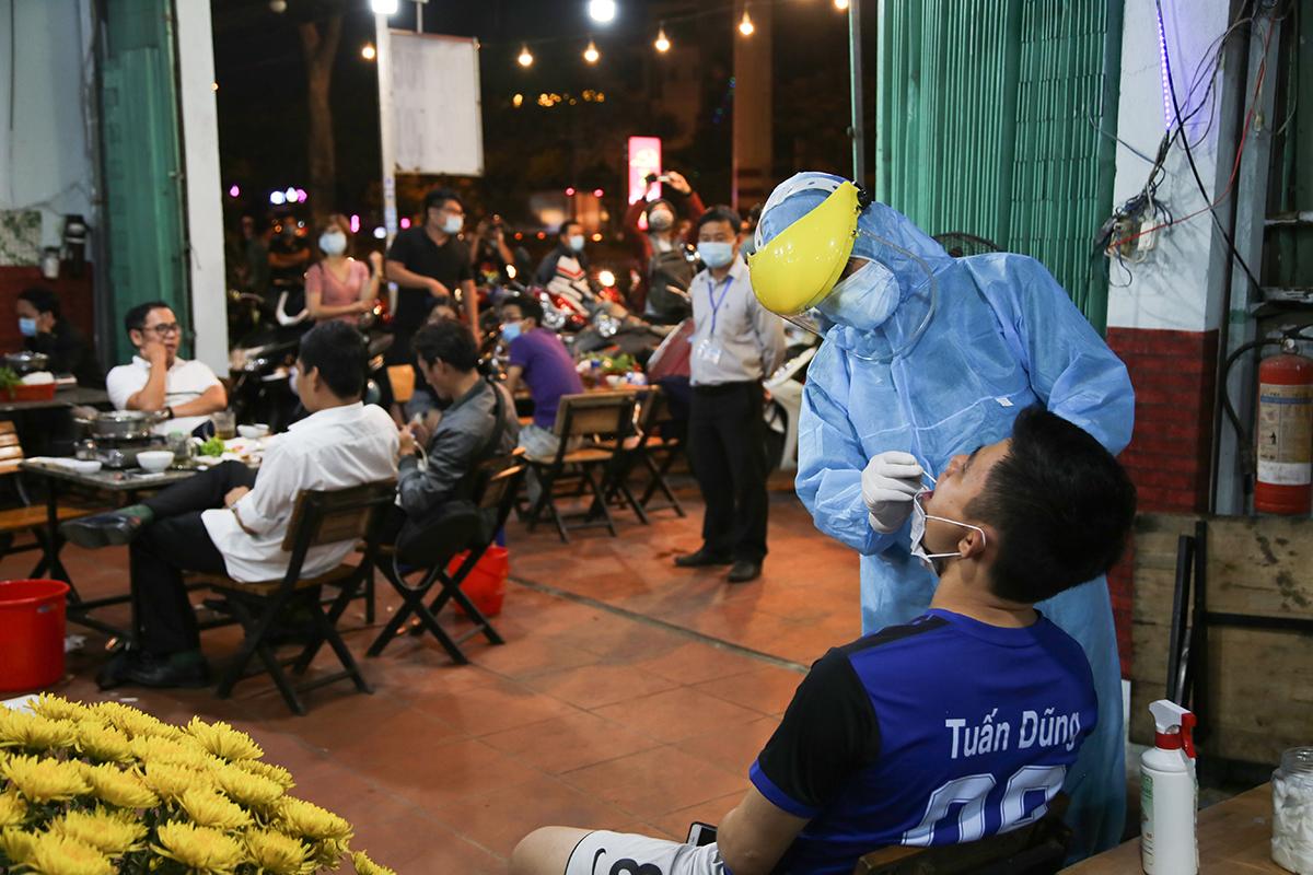 Nhân viên y tế lấy mẫu phết mũi họng thực khách ở quán nhậu, tối 22/2. Ảnh: Đình Văn.