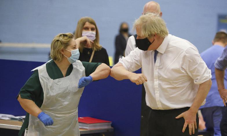 Thủ tướng Anh Boris Johnson (phải) đến thăm một trung tâm tiêm chủng ở Cwmbran, miền nam xứ Wales hôm 17/2. Ảnh: AFP.