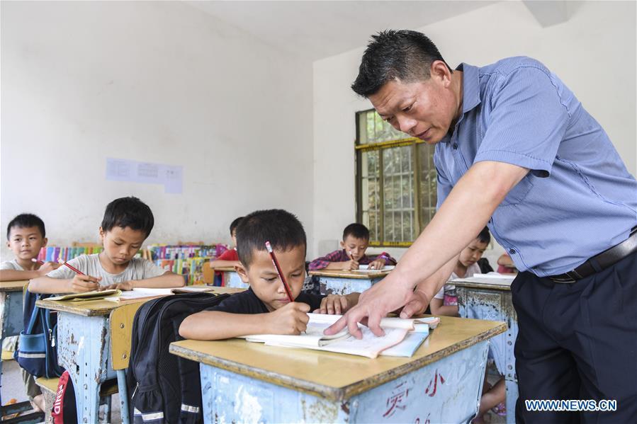 Thầy Jiao Shengding, giáo viên ở thị trấn Aidian, Quảng Tây, miền Nam Trung Quốc, đang dạy kèm học sinh, ngày 22/6/2020. Ảnh: Xinhua