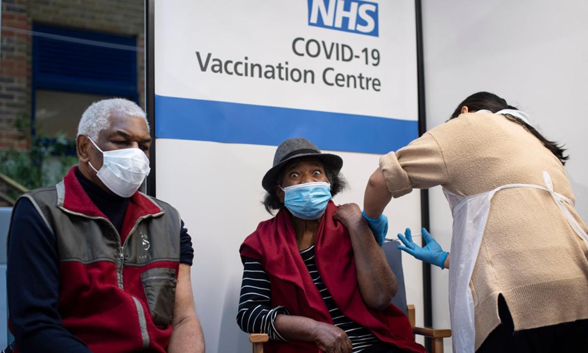 Nhân viên y tế tiêm vaccine Covid-19 cho người cao tuổi tại Bệnh viện Guys ở London, Anh tháng 12/2020. Ảnh: AP.