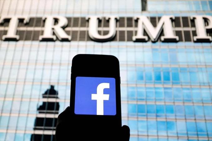 Một người giơ logo Facebook trước tòa nhà của Trump. Ảnh: Reuters.