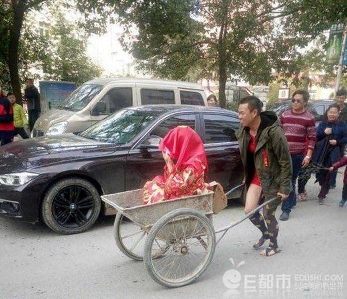 Hình ảnh chú rể mặc quần sooc, rước dâu bằng xe cút kít từng gây sốt trên MXH Trung Quốc. Thay bằng xe hơi sang trọng, chàng trai nghèo này dùng chiếc xe phụ hồ cũ kỹ để đón dâu.