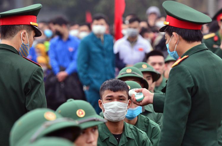Kiểm tra thân nhiệt các tân binh tại lễ giao quân của huyện Đông Anh, Hà Nội năm 2020. Ảnh: Võ Hải.
