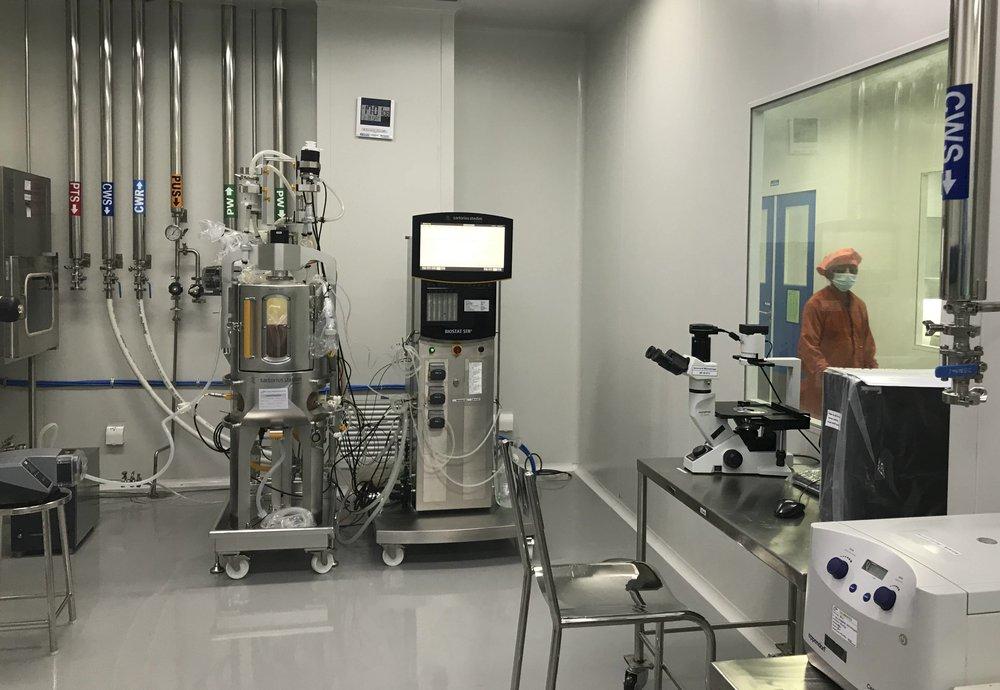 Nhân viên nhà máy Incepta đi qua một căn phòng chứa máy móc sản xuất vaccine hiện đại hôm 13/2. Ảnh: AP