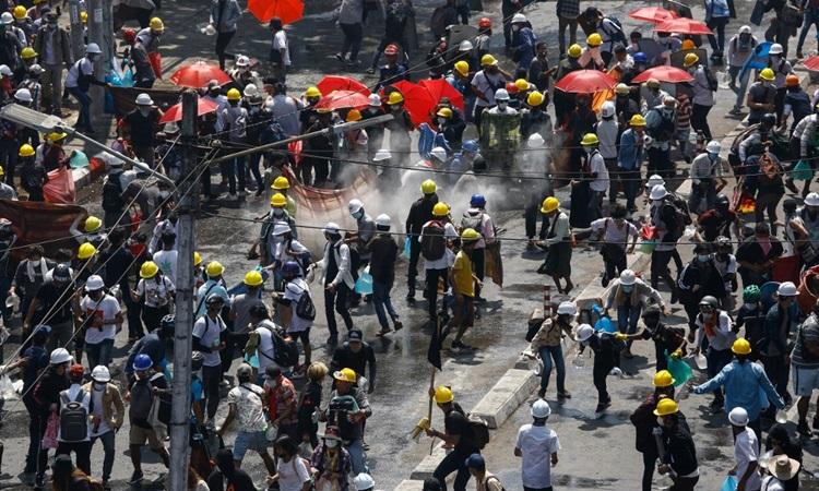 Người biểu tình Myanmar ở thành phố Yangon phản ứng sau khi bị cảnh sát xịt hơi cay hôm 1/3. Ảnh: AFP.