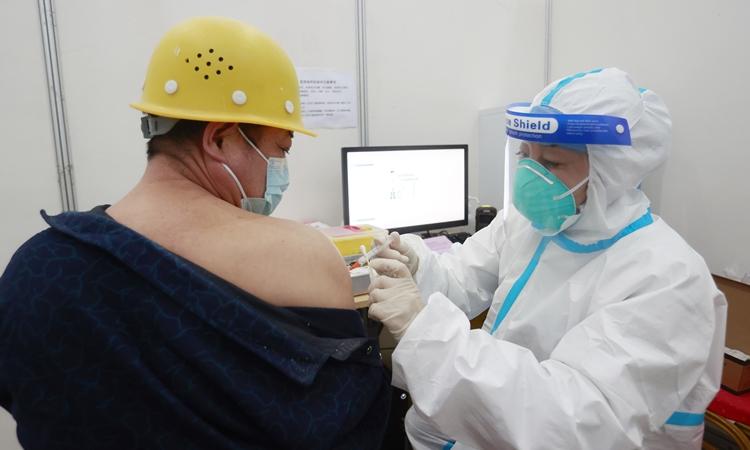 Nhân viên y tế tiêm vacine cho một công nhân tại Diên Khánh, Bắc Kinh, Trung Quốc hôm 2/3. Ảnh: Reuters.