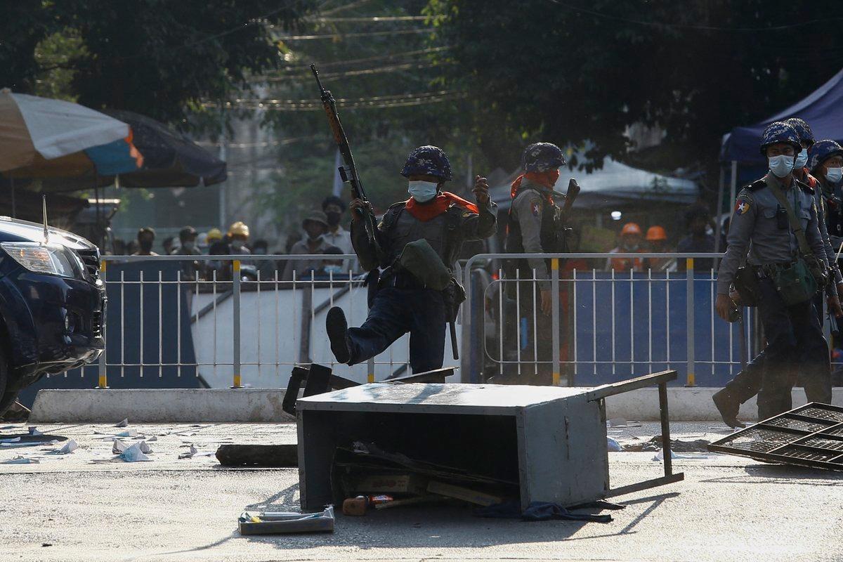Cảnh sát đá vào rào chắn người biểu tình dựng lên tại một con đường ở Yangon ngày 2/3. Ảnh: Reuters.