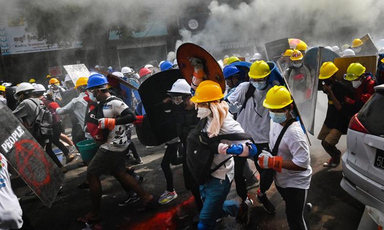 Người biểu tình dùng khiên tự chế để che chắn khi cảnh sát sử dụng hơi cay giải tán đám đông ở thành phố Yangon hôm nay. Ảnh: AFP.