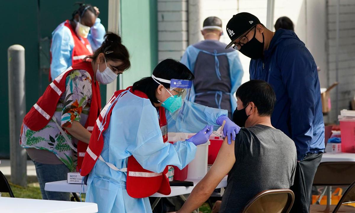 Nhân viên y tế tiêm chủng vaccine Covid-19 cho người dân tại Pacoima, California hôm 13/1. Ảnh: AP.