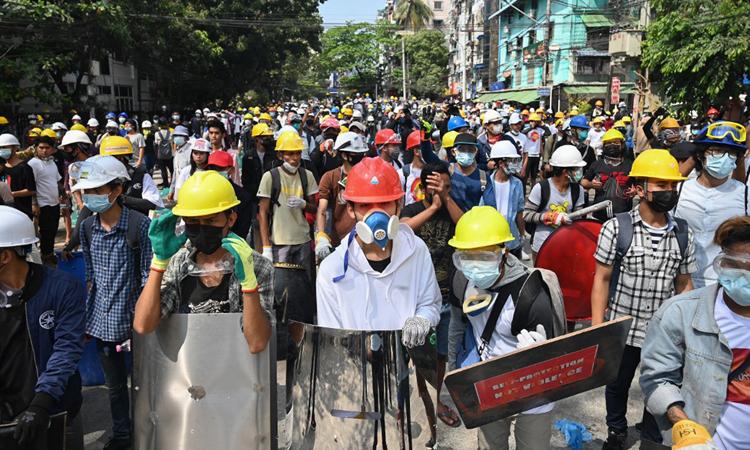 Người biểu tình mang đồ bảo hộ, tập trung trên một con phố ở thành phố Yangon, Myanmar hôm 3/3. Ảnh: AFP.