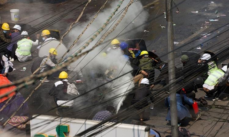 Người biểu tình phản ứng khi bị cảnh sát xịt hơi cay ở thành phố Mandalay hôm 3/3. Ảnh: AFP.