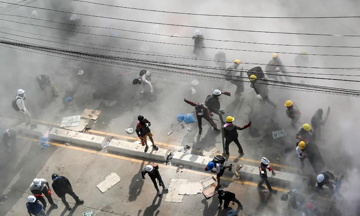 Người biểu tình ứng hơi cay của lực lượng an ninh ở thành phố Yangon, Myanmar, ngày 4/3. Ảnh: AFP.