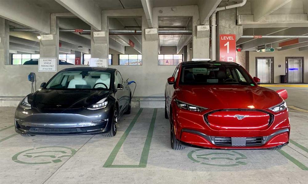 Ford Mustang Mach E (xe đỏ) đỗ cạnh Tesla Model 3 tại một bãi đỗ xe có sạc dành cho xe điện ở Dearborn, Michigan, trong năm 2020. Ảnh: Inside EVs