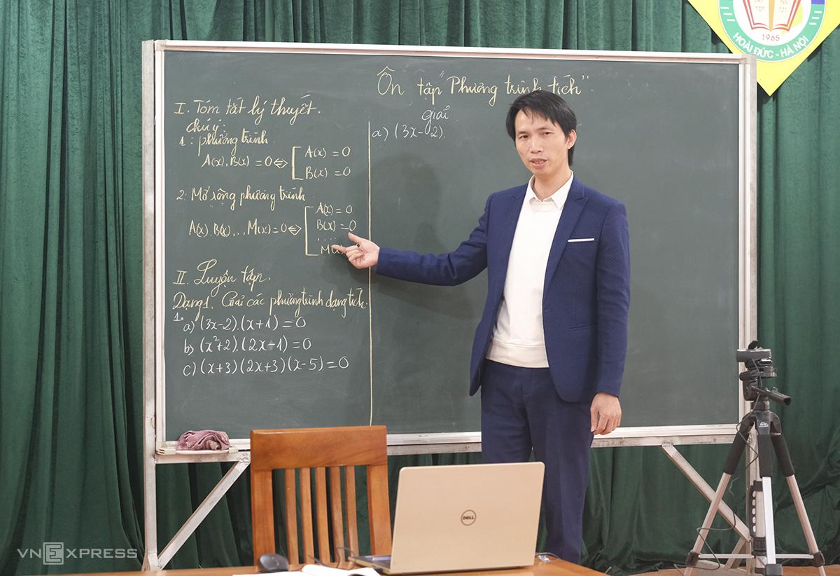Thầy Nguyễn Văn Thanh, giáo viên Toán dạy trực tuyến với sự hỗ trợ của máy tính, điện thoại cá nhân và camera do nhà trường trang bị. Ảnh: Dương Tâm.