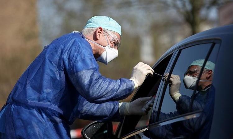 Bác sĩ lấy mẫu xét nghiệm Covid-19 qua cửa sổ xe hơi tại Halle, phía đông Đức, hồi tháng ba năm ngoái. Ảnh: Reuters.