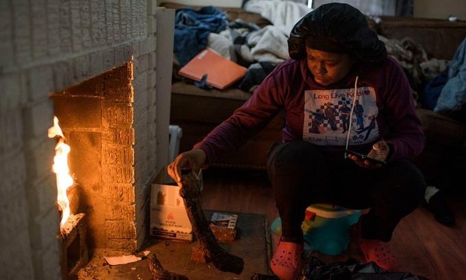 Một người dân ở Houston, Texas, đốt củi sưởi ấm hôm 17/2. Ảnh: Washington Post