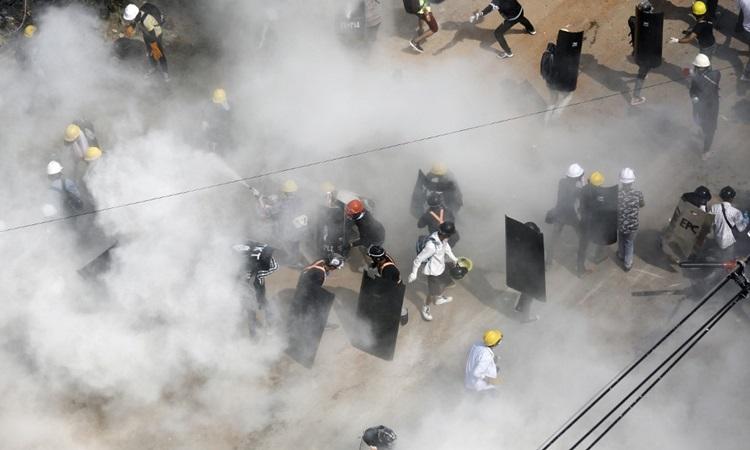Người biểu tình phản ứng khi bị cảnh sát xịt hơi cay ở Yangon, Myanmar hôm 6/3. Ảnh: AFP.