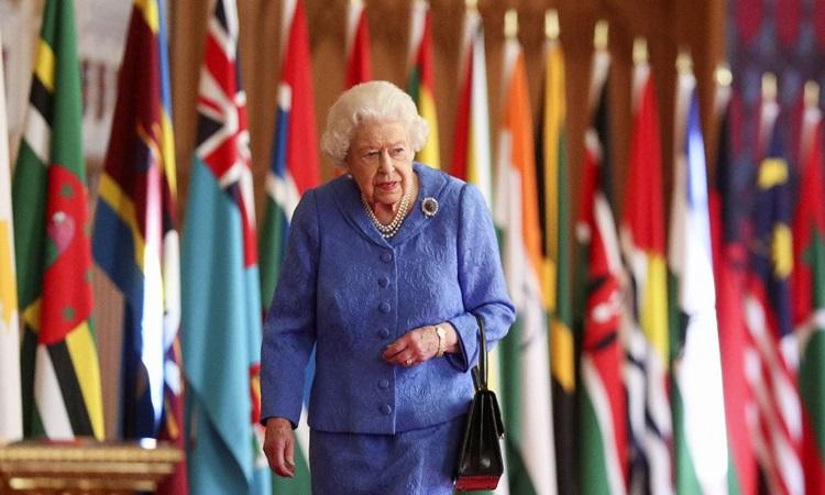 Nữ hoàng Anh Elizabeth đi ngang qua các lá cờ của Khối thịnh vượng chung được trưng bày trong sảnh lâu đài Windsor, đông nam nước Anh hôm 5/3. Ảnh: AFP.