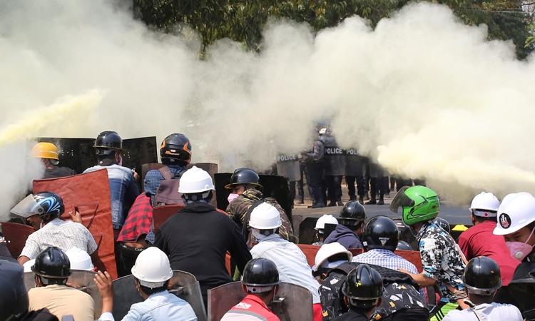 Người biểu tình Myanmar dựng khiên tự chế tránh lựu đạn khói và đạn hơi cay của cảnh sát ở Naypyitaw hôm nay. Ảnh: Reuters.