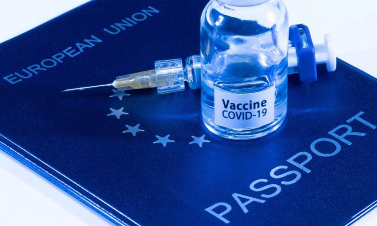 Ảnh minh họa hộ chiếu Liên minh châu Âu và lọ vaccine Covid-19. Ảnh: AFP.