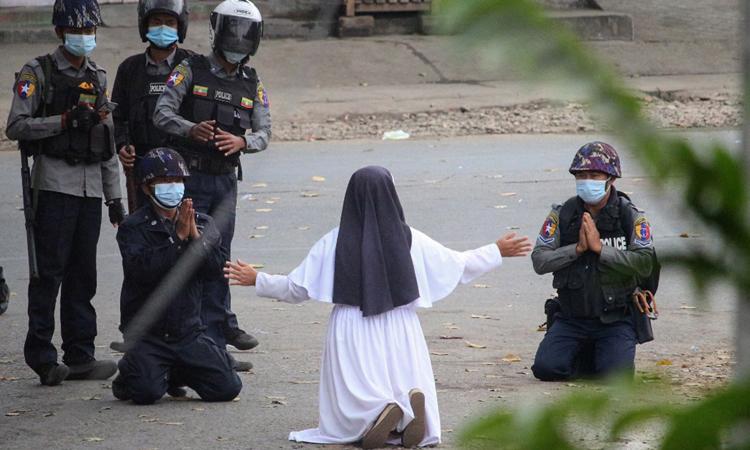 Nữ tu Ann Roza quỳ trước cảnh sát ở thành phố Myitkyina, bang Kachin hôm 8/3, trong khi hai cảnh sát cũng quỳ với bà. Ảnh: AFP.