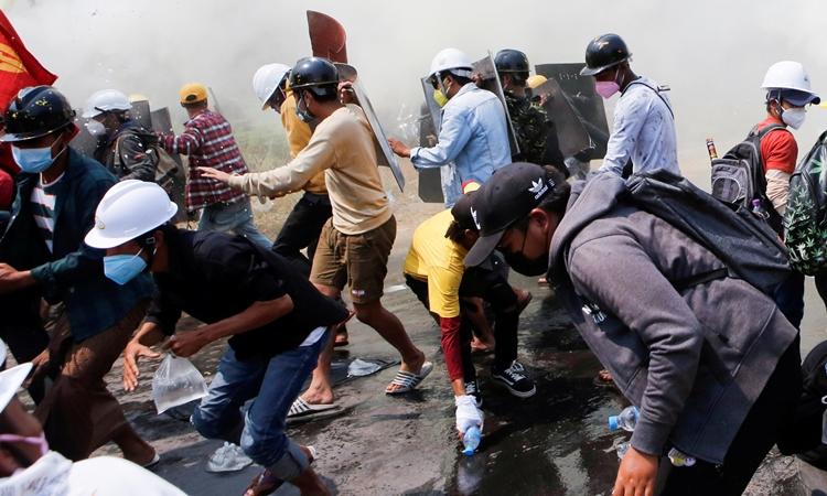 Người biểu tình Myanmar tháo chạy khi lực lượng an ninh dùng hơi cay và lựu đạn khói ở Naypyitaw hôm 8/3. Ảnh: Reuters.