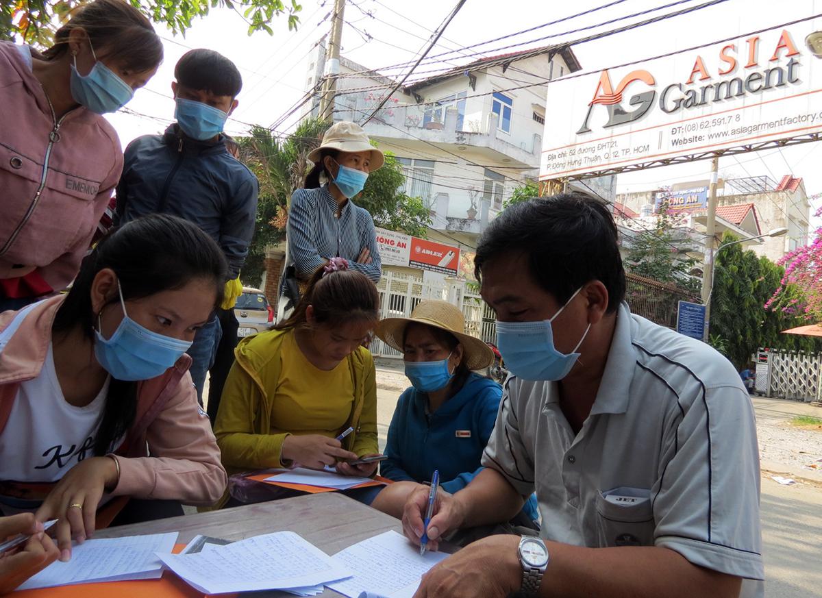 Công nhân viết đơn khởi kiện Công ty TNHH Asia Garment, ngày 10/3. Ảnh: Lê Tuyết.