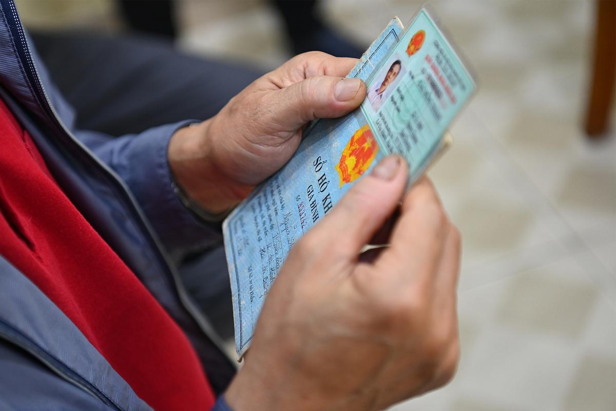 Một người dân cầm chứng minh thư và hộ khẩu giấy đi làm thẻ căn cước công dân gắn chip, ngày 9/3. Ảnh: Giang Huy